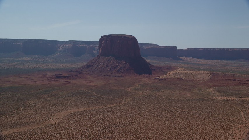 Flying by Mitchell Butte, desert, Monument Valley, Utah, Arizona Aerial Stock Footage | AX135_005