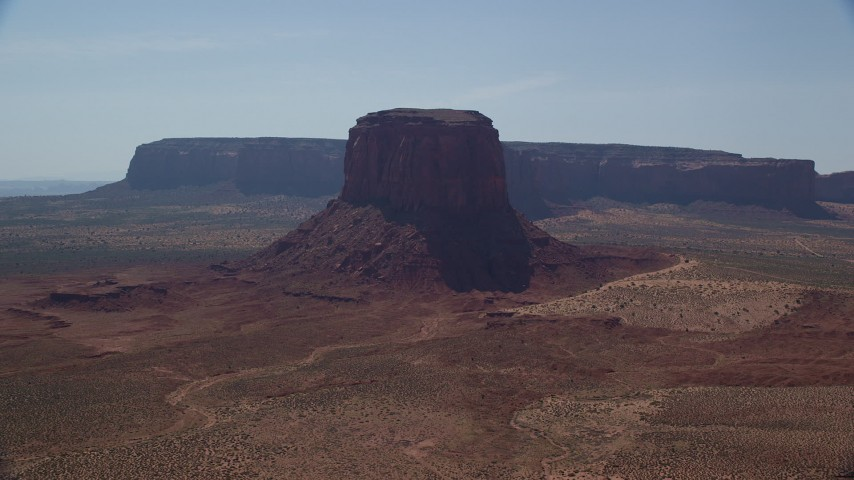 6K stock footage aerial video of passing by Mitchell Butte and desert, Monument Valley, Utah, Arizona Aerial Stock Footage | AX135_006