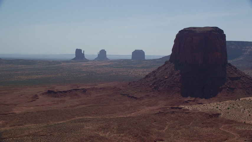 6K stock footage aerial video of flying by buttes in hazy desert valley, Monument Valley, Utah, Arizona, sunset Aerial Stock Footage | AX135_007