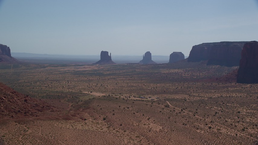 6K stock footage aerial video of a wide view of buttes in a hazy desert valley, Monument Valley, Utah, Arizona Aerial Stock Footage | AX135_009