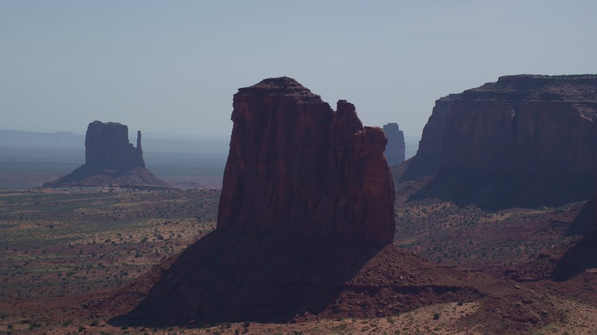 Flying by Gray Whiskers Butte, West Mitten Butte, Monument Valley, Utah, Arizona  Aerial Stock Footage | AX135_010