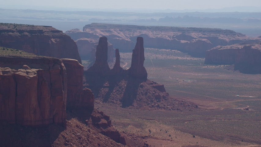 Flying by Three Sisters, buttes, mesas, Monument Valley, Utah, Arizona Aerial Stock Footage | AX135_014