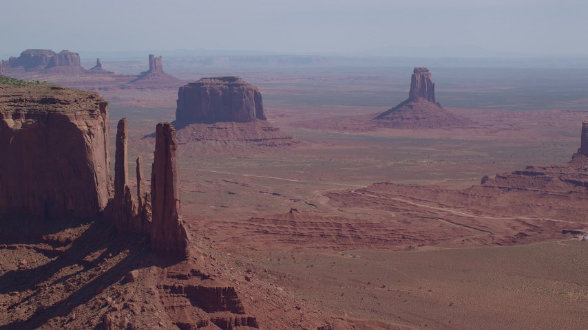 Flying by Three Sisters, buttes in the background, Monument Valley, Utah, Arizona Aerial Stock Footage | AX135_018