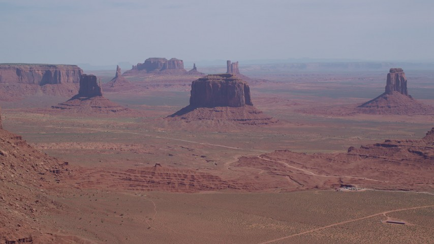 6K stock footage aerial video of a wide view of flying by buttes and hazy desert, Monument Valley, Utah, Arizona Aerial Stock Footage | AX135_019