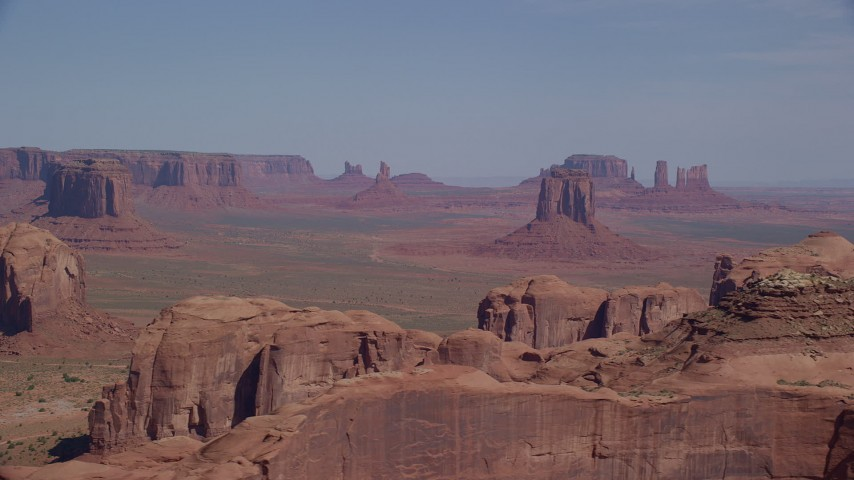 Flying by East Mitten Butte, distant buttes, Monument Valley, Utah, Arizona Aerial Stock Footage | AX135_024
