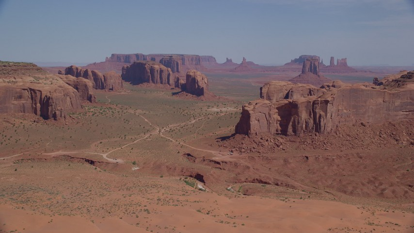 Flying by buttes and mesas, desert valley, Monument Valley, Utah, Arizona Aerial Stock Footage | AX135_026