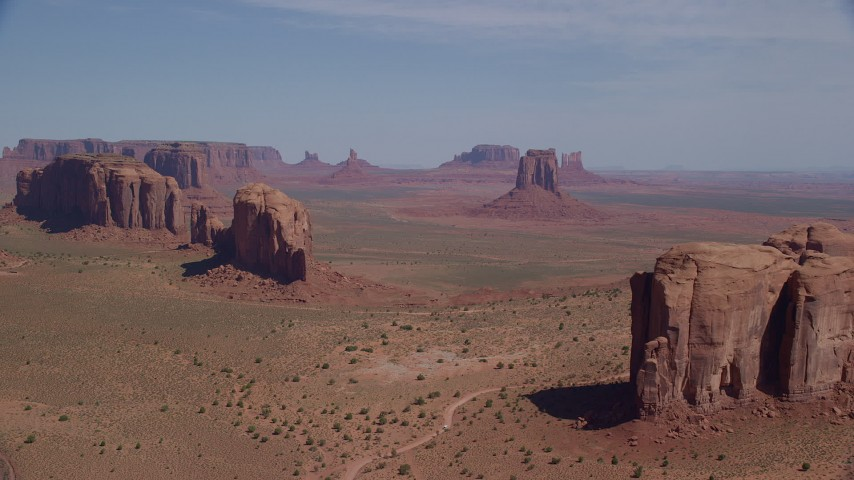 Approaching buttes, hazy desert valley, Monument Valley, Utah, Arizona Aerial Stock Footage | AX135_029