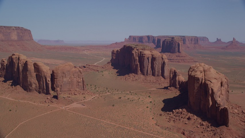 Approaching buttes, hazy desert valley, Monument Valley, Utah, Arizona Aerial Stock Footage | AX135_030