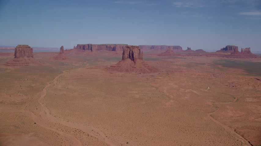 Flying by buttes and mesas, desert valley, Monument Valley, Utah, Arizona Aerial Stock Footage | AX135_035