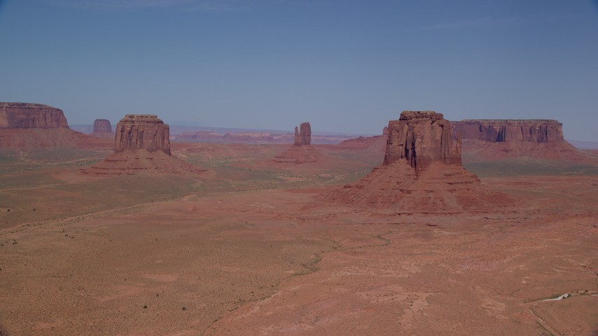6K stock footage aerial video of slowly passing buttes in a desert valley, Monument Valley, Utah, Arizona Aerial Stock Footage | AX135_036