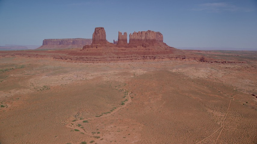 6K stock footage aerial video of approaching buttes surrounded by desert valley; Monument Valley, Utah, Arizona Aerial Stock Footage | AX135_043