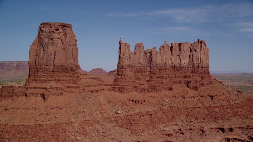 Flying by buttes in a desert valley, Monument Valley, Utah, Arizona Aerial Stock Footage AX135_046