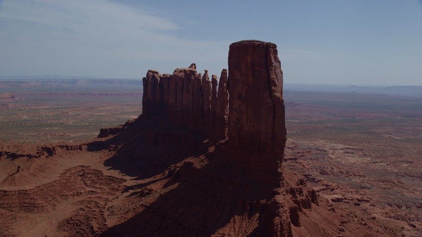 Flying by buttes surrounded by desert valley, Monument Valley, Utah, Arizona Aerial Stock Footage AX135_048