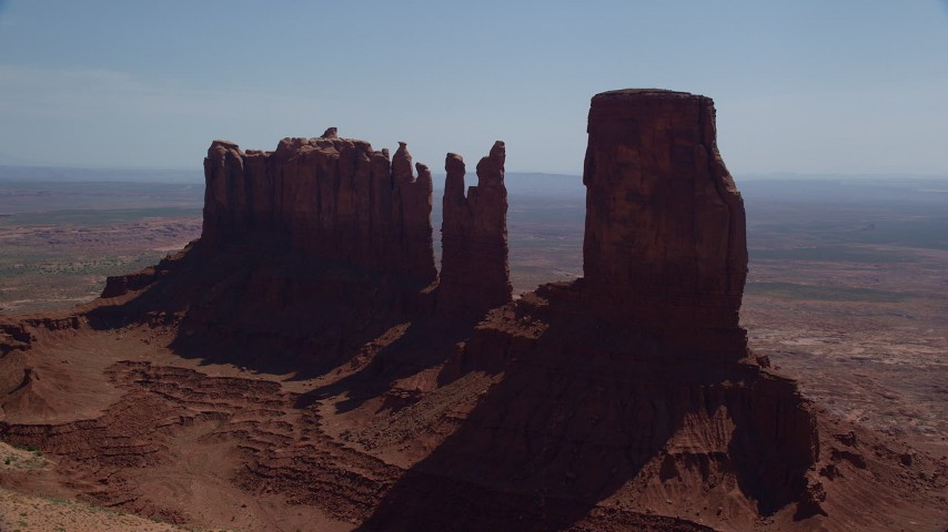 Flying by buttes surrounded by a desert valley, Monument Valley, Utah, Arizona Aerial Stock Footage | AX135_049
