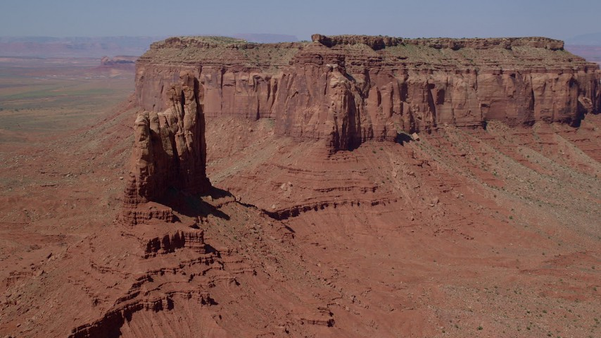 Orbiting Setting Hen Butte, near Eagle Mesa, Monument Valley, Utah, Arizona Aerial Stock Footage | AX135_052