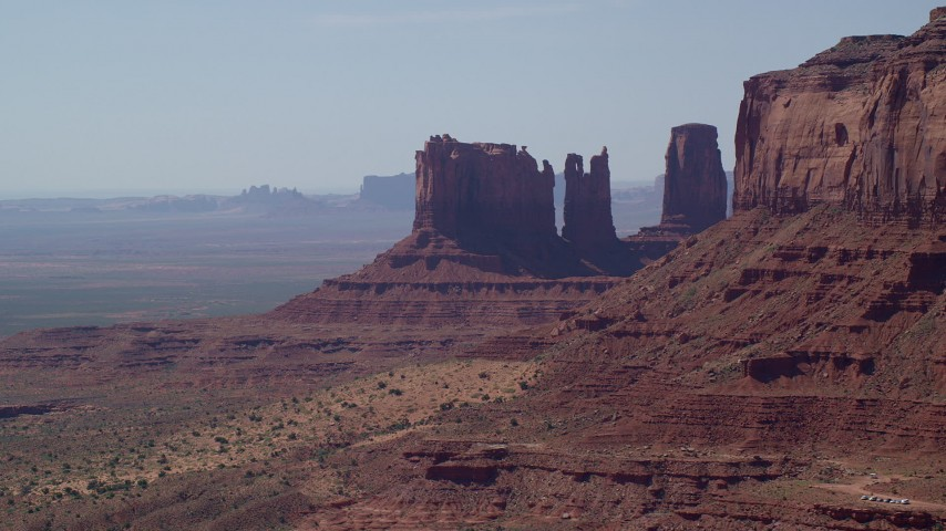 Flying by buttes, ,hazy desert valley, Monument Valley, Utah, Arizona Aerial Stock Footage | AX135_063