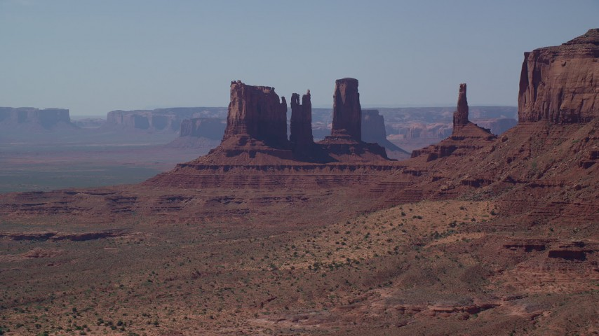 Flying by buttes, desert valley, Monument Valley, Utah, Arizona Aerial Stock Footage | AX135_064