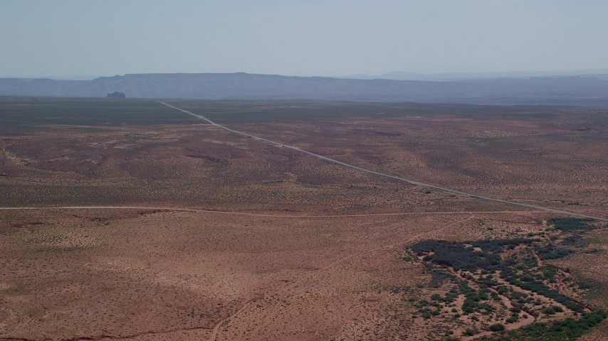 6K stock footage aerial video of approaching Highway 163 through desert valley, Monument Valley, Utah, Arizona Aerial Stock Footage | AX135_070