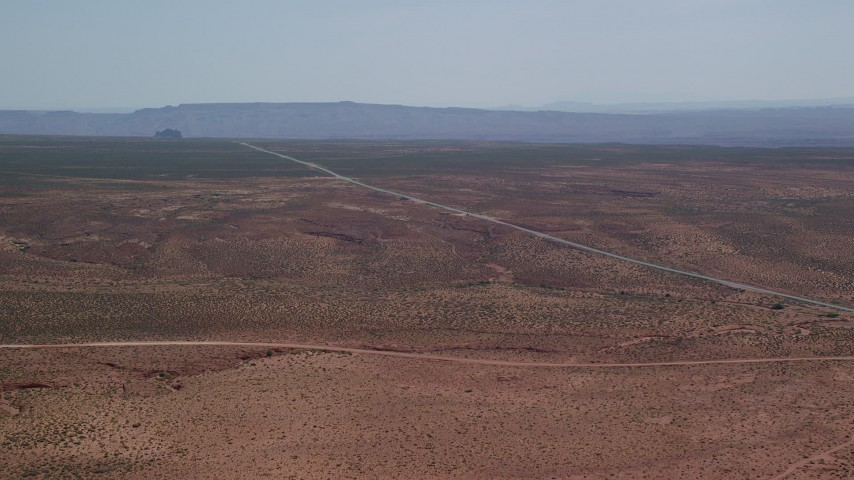 Approaching Highway 163, desert valley, Monument Valley, Utah, Arizona Aerial Stock Footage | AX135_071