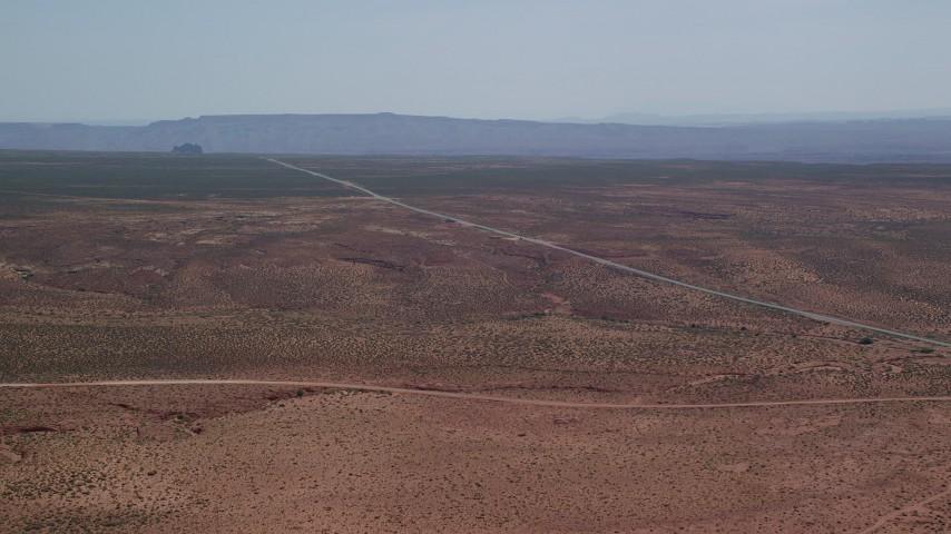 6K stock footage aerial video of flying toward Highway 163 in desert valley, Monument Valley, Utah, Arizona Aerial Stock Footage | AX135_071