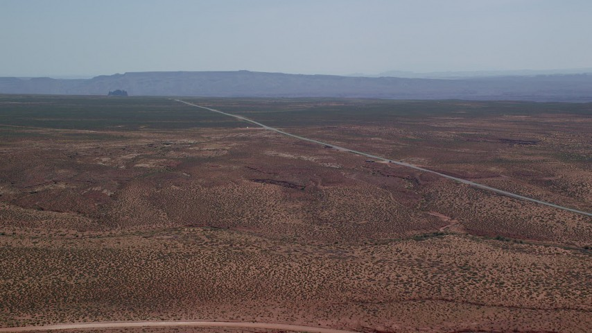 Approaching Highway 163, desert valley, Monument Valley, Utah, Arizona Aerial Stock Footage | AX135_072