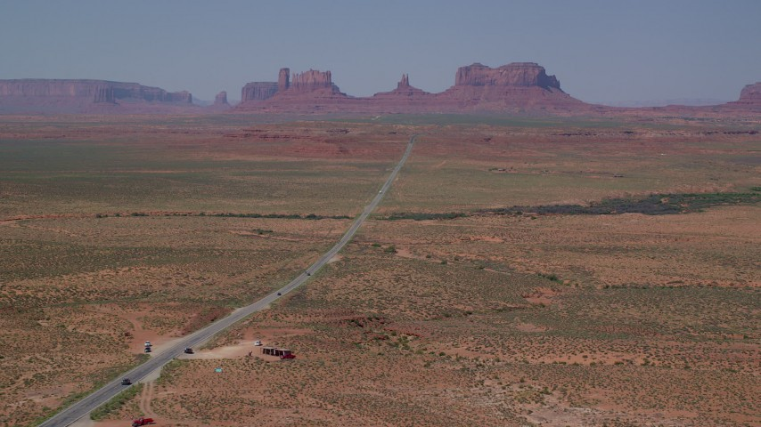 6K stock footage aerial video of flying over Forrest Gump Point by Highway 163, approach distant buttes in Monument Valley, Utah, Arizona Aerial Stock Footage | AX135_076