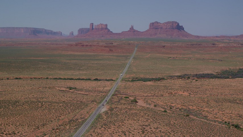 Flying by Highway 163, approaching buttes, Monument Valley, Utah, Arizona Aerial Stock Footage | AX135_077