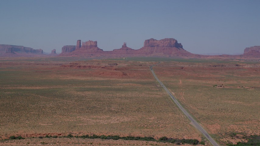 6K stock footage aerial video of passing by distant buttes, seen from Highway 163, Monument Valley, Utah, Arizona Aerial Stock Footage | AX135_078