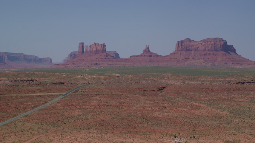 Flying by Highway 163 leading to desert buttes, Monument Valley, Utah, Arizona Aerial Stock Footage | AX135_080