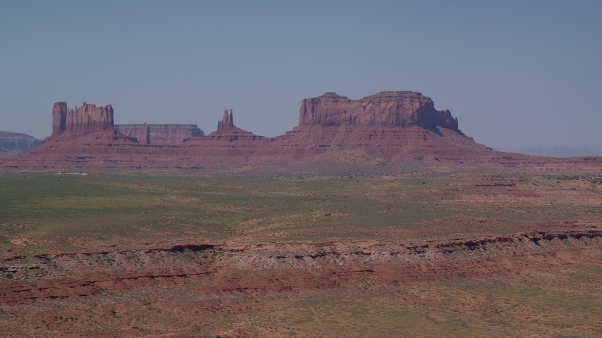 Flying by buttes across a desert valley, Monument Valley, Utah, Arizona Aerial Stock Footage | AX135_082