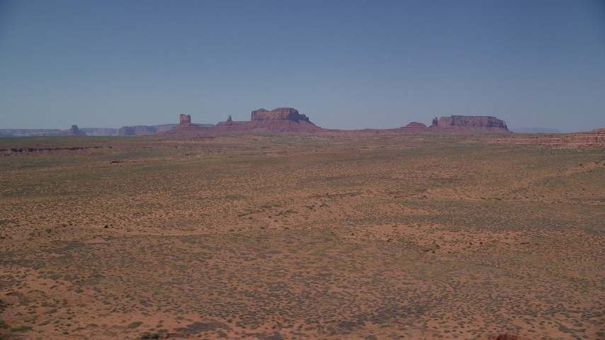 Flying by distant buttes, desert valley, Monument Valley, Utah, Arizona Aerial Stock Footage | AX135_083
