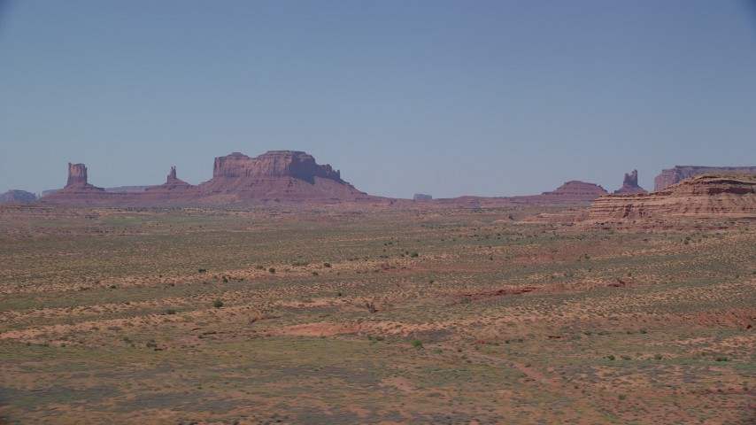 6K stock footage aerial video of passing distant buttes in an open desert valley, Monument Valley, Utah, Arizona Aerial Stock Footage | AX135_085