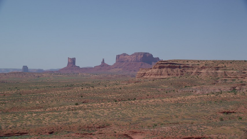 Flying by distant buttes, desert valley, Monument Valley, Utah, Arizona Aerial Stock Footage | AX135_086