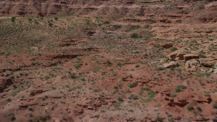 Flying low over desert, approaching a butte, Monument Valley, Utah, Arizona Aerial Stock Footage | AX135_087
