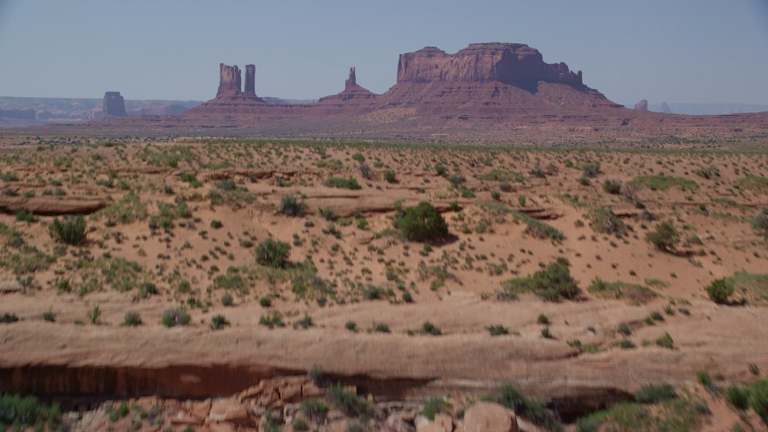 6K stock footage aerial video of flying low over butte, revealing distant buttes in Monument Valley, Utah, Arizona Aerial Stock Footage | AX135_088