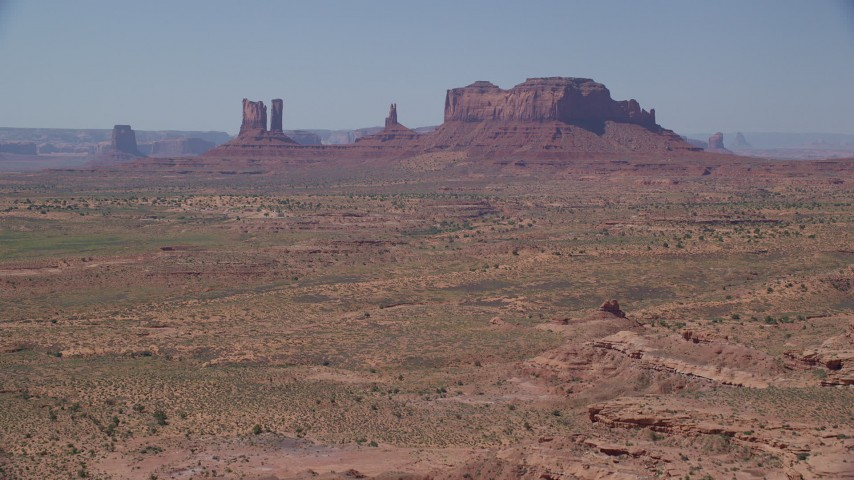 Approaching buttes across a desert valley, Monument Valley, Utah, Arizona Aerial Stock Footage | AX135_089