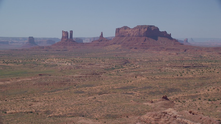 6K stock footage aerial video of approaching several buttes across a desert valley, Monument Valley, Utah, Arizona Aerial Stock Footage | AX135_089