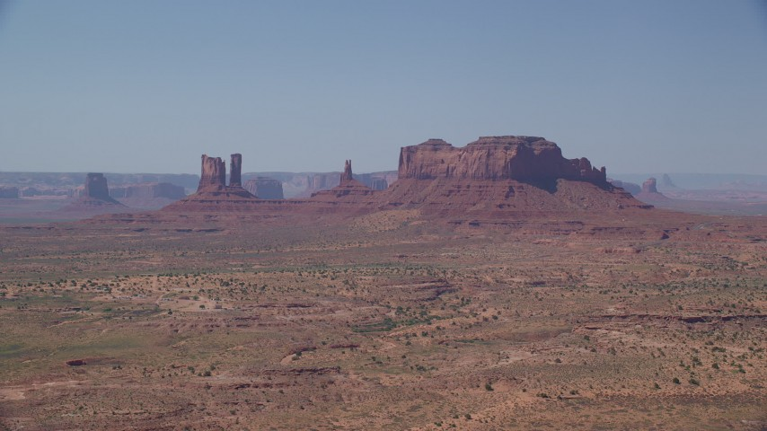 6K stock footage aerial video of flying toward several buttes across hazy desert valley, Monument Valley, Utah, Arizona Aerial Stock Footage | AX135_090