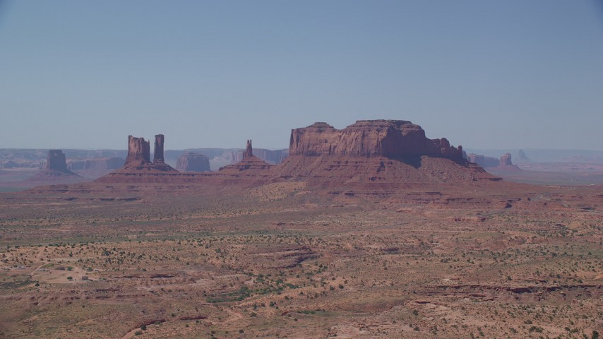 Flying by buttes across hazy desert valley, Monument Valley, Utah, Arizona Aerial Stock Footage | AX135_091