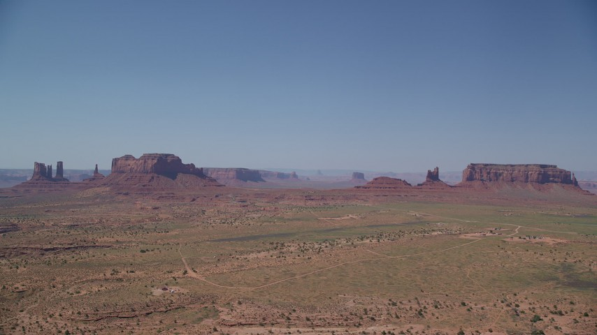 Flying by desert buttes and mesas, Monument Valley, Utah, Arizona Aerial Stock Footage | AX135_092