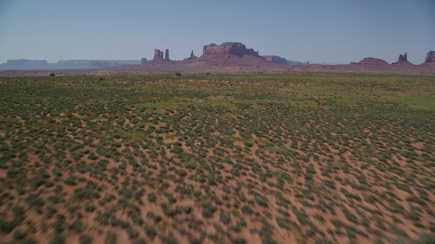 Flying low over desert, tilt up, reveal buttes, Monument Valley, Utah, Arizona Aerial Stock Footage | AX135_093