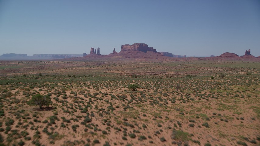 Approaching buttes across desert valley, Monument Valley, Utah, Arizona Aerial Stock Footage | AX135_094