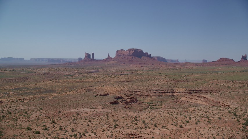 Approaching distant buttes, across desert valley, Monument Valley, Utah, Arizona Aerial Stock Footage | AX135_095