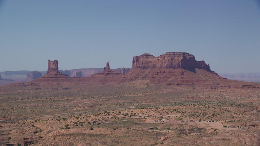 Flying by buttes across desert valley, Monument Valley, Utah, Arizona Aerial Stock Footage | AX135_102