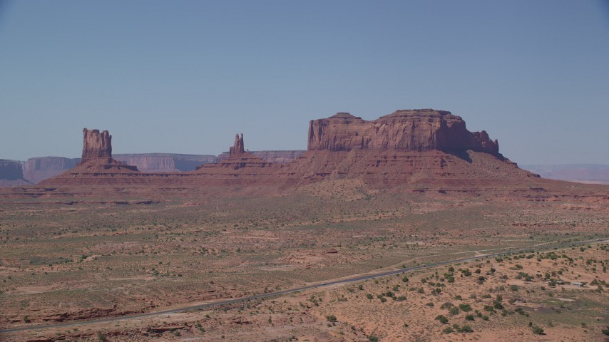 6K stock footage aerial video of flying by buttes, with Highway 163 in the foreground, Monument Valley, Utah, Arizona Aerial Stock Footage | AX135_103