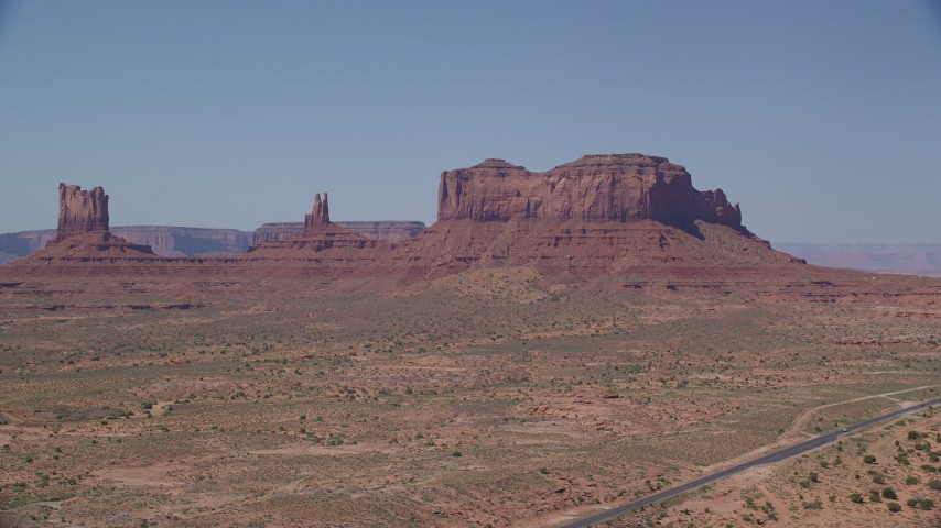 Flying by buttes, desert valley, Monument Valley, Utah, Arizona Aerial Stock Footage | AX135_104
