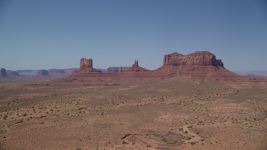 6K stock footage aerial video of approaching butte across desert valley, Monument Valley, Utah, Arizona Aerial Stock Footage | AX135_105