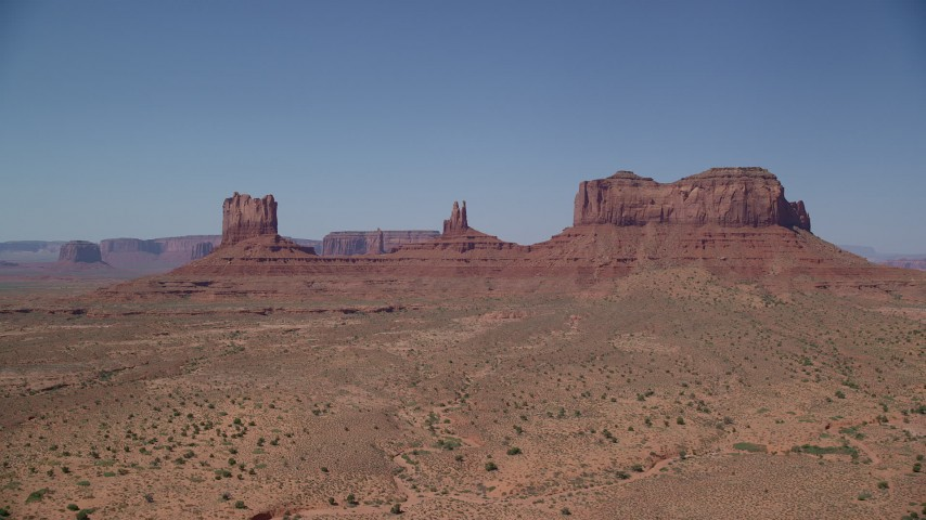 Approaching buttes across a desert valley, Monument Valley, Utah, Arizona Aerial Stock Footage | AX135_106