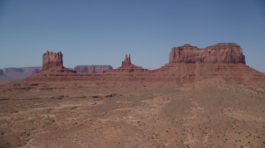 Approaching buttes across a desert valley, Monument Valley, Utah, Arizona Aerial Stock Footage | AX135_107