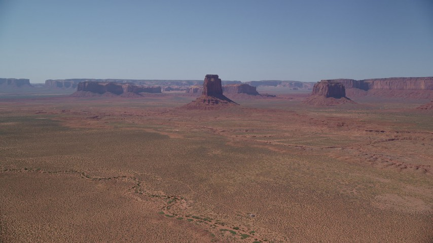 6K stock footage aerial video of approaching East Mitten Butte across desert valley, Monument Valley, Utah, Arizona Aerial Stock Footage | AX135_112